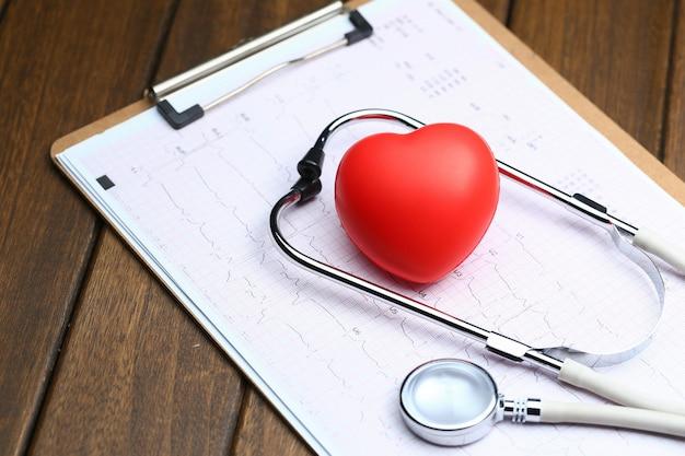 Coração vermelho com estetoscópio e eletrocardiograma em fundo de madeira