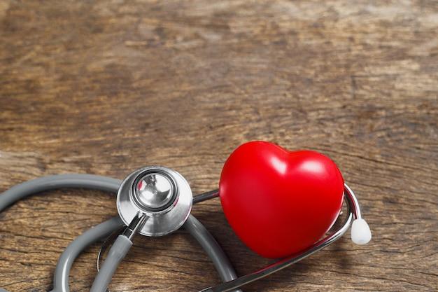 Coração vermelho com estetoscópio na mesa de madeira. examinando o pulso de batimentos cardíacos do paciente. tratamento cardiológico. conceito de saúde e cuidados.