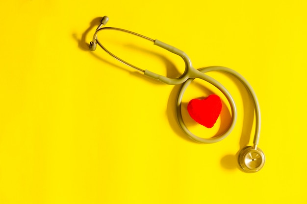 Coração vermelho com estetoscópio, saúde do coração, conceito de seguro de saúde
