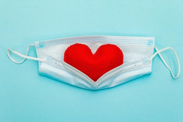 Coração vermelho com máscara de proteção médica em fundo azul claro, vista superior, copie o espaço. conceito de saúde, autodefesa