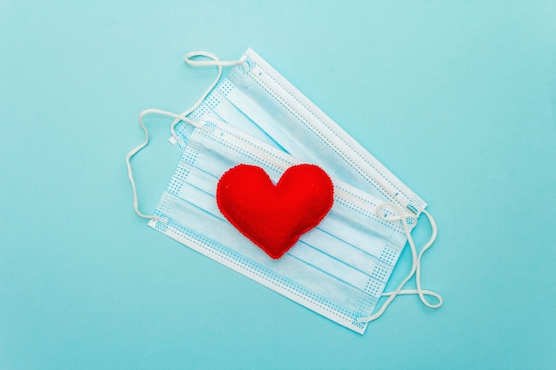 Coração vermelho com máscaras de proteção médica em fundo azul claro, vista superior, copie o espaço. conceito de saúde, autodefesa