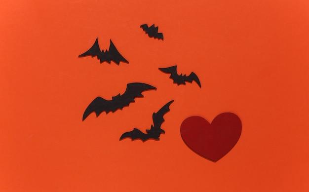 Coração vermelho com morcegos e aranhas em fundo laranja brilhante. tema de halloween.