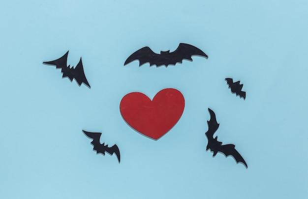 Coração vermelho com morcegos e aranhas sobre fundo azul brilhante. tema de halloween.