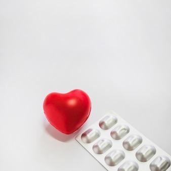 Coração vermelho, com, prata, embalado, pílulas, branco, fundo