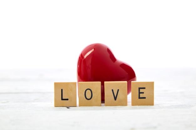 Coração vermelho com texto de dia dos namorados amor blocos de letras de madeira na mesa branca