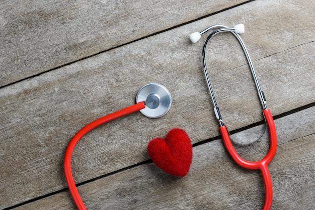 Coração vermelho com um estetoscópio na mesa de madeira