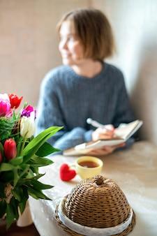 Coração vermelho de malha e uma xícara de chá na mesa com uma garota segurando o caderno. cozinha
