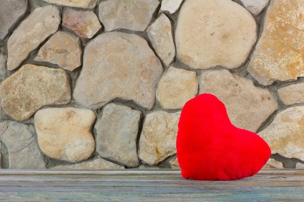 Coração vermelho de pelúcia no fundo de uma parede de pedra, o conceito de amor e romance