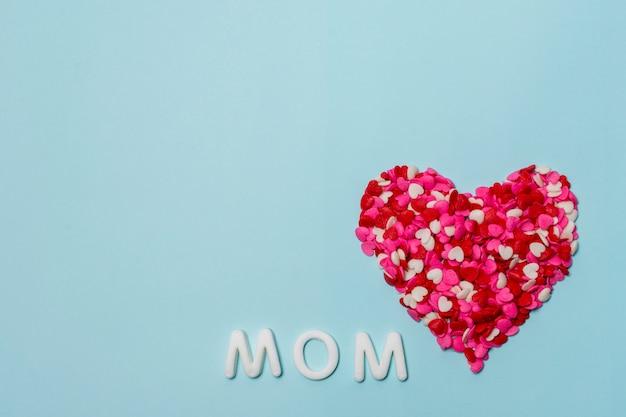Coração vermelho de pequenas decorações perto da palavra mãe