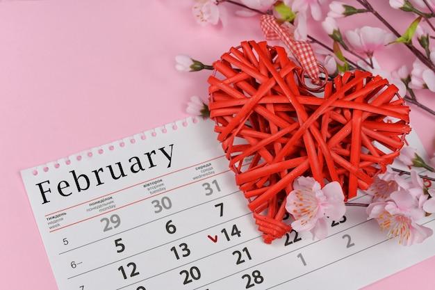 Coração vermelho de vime com flores rosa e calendário