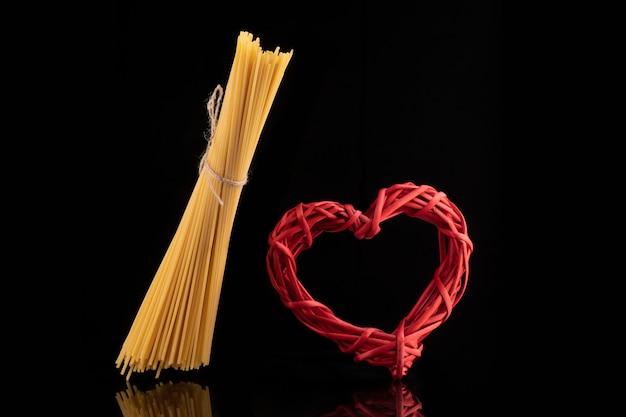 Coração vermelho de vime e bando de espaguete seco cru em fundo preto isolado.