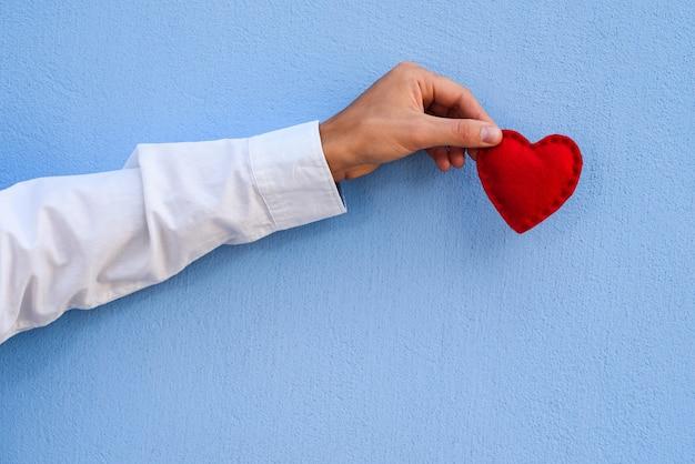 Coração vermelho decorativo na mão de um cara sobre um fundo azul. cartão de feriado do dia dos namorados