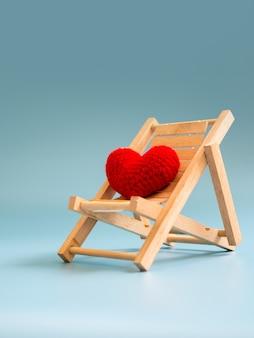 Coração vermelho do fio na cadeira de praia de madeira no fundo de tela azul