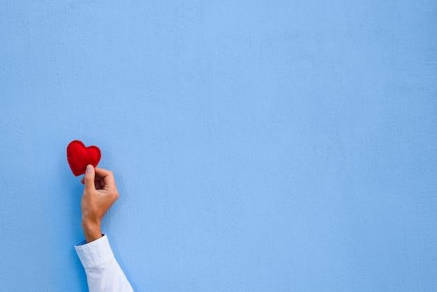 Coração vermelho dos namorados em um homem com a mão no fundo da parede azul