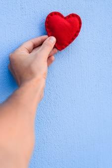 Coração vermelho dos namorados na mão de um cara em um fundo azul