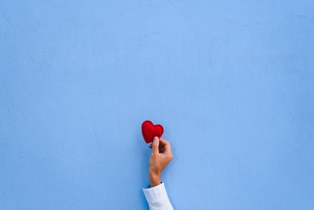 Coração vermelho dos namorados na mão de um homem no fundo da parede azul. cartão com espaço de cópia para texto