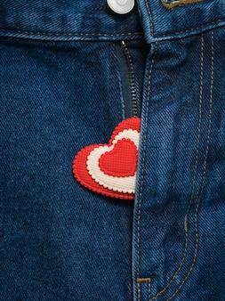 Coração vermelho e branco saindo da calça jeans aberta.