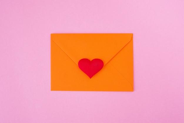 Coração vermelho e envelope em fundo rosa