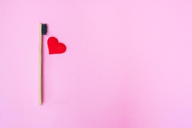 Coração vermelho e escova de dentes de bambu com espaço de cópia em fundo rosa