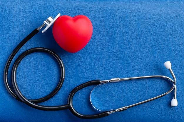 Coração vermelho e estetoscópio na mesa azul