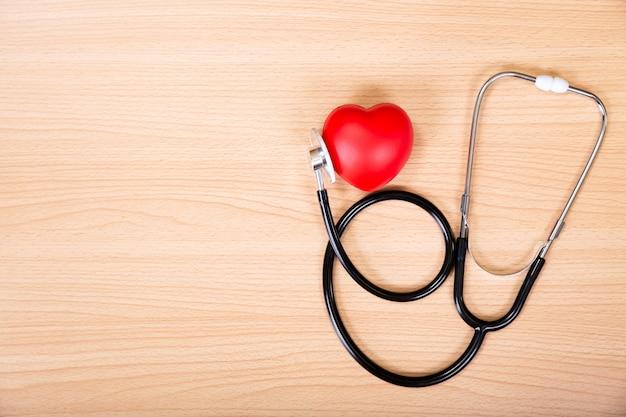 Coração vermelho e estetoscópio na mesa de madeira.