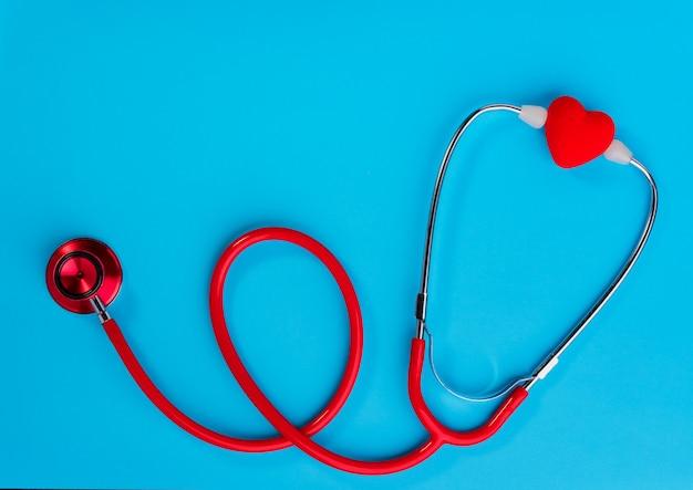 Coração vermelho e estetoscópio sobre azul.