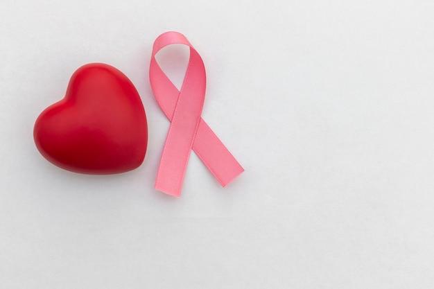 Coração vermelho e fita rosa. campanha de prevenção do câncer de mama.