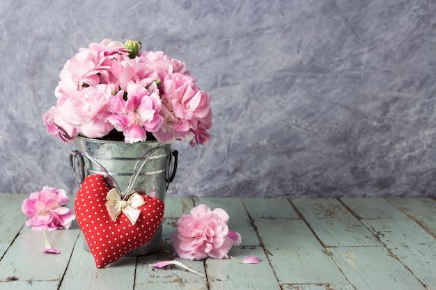 Coração vermelho e flores de cravo-de-rosa no balde de zinco na madeira velha