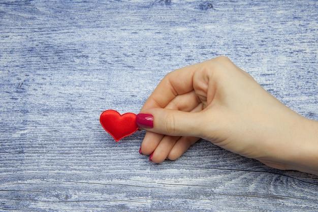 Coração vermelho e mão feminina segurando, conceito de amor eterno