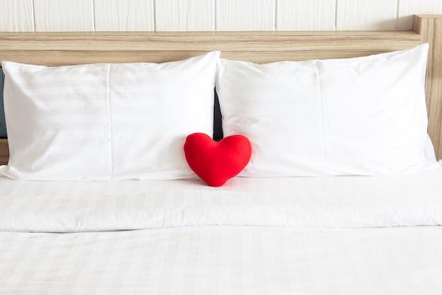 Coração vermelho e o travesseiro branco dos pares na cama para o conceito do dia do amor, do casamento e do valentim