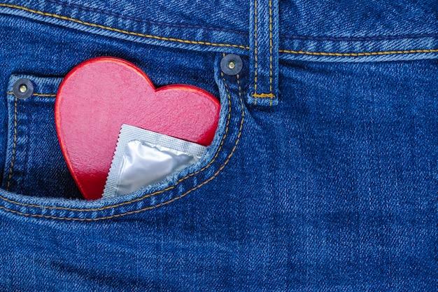 Coração vermelho e preservativo no bolso da calça jeans. plano de fundo para o dia dos namorados.