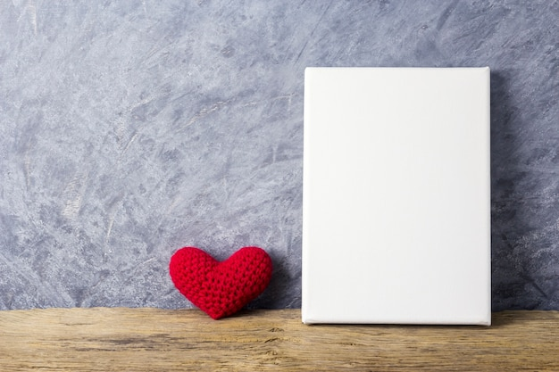 Coração vermelho e quadro de tela em branco na mesa de madeira para dia dos namorados e casamento