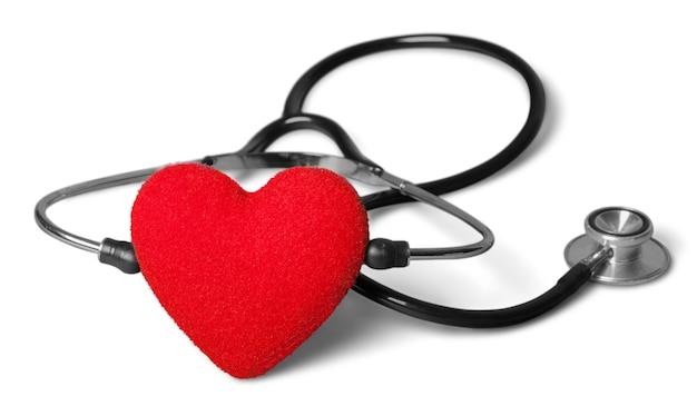 Coração vermelho e um estetoscópio no fundo