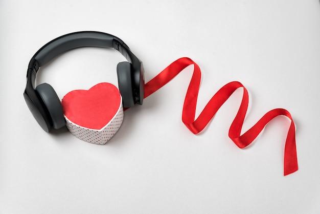 Coração vermelho em forma de fones de ouvido estéreo e uma fita vermelha. ouça o seu coração. música do coração