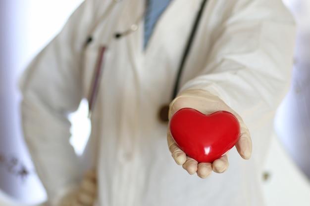 Coração vermelho em forma de médico, mão na luva
