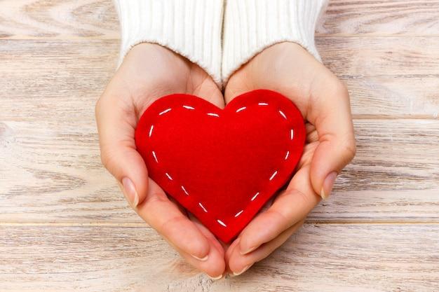 Coração vermelho em mãos closeup em fundo de madeira
