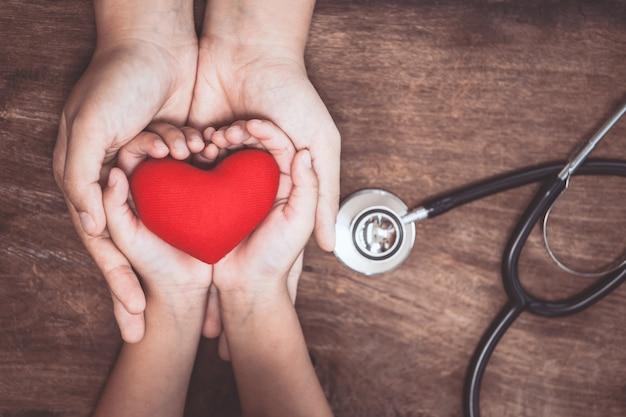 Coração vermelho em mãos de mulher e criança e com estetoscópio de médico em fundo de madeira