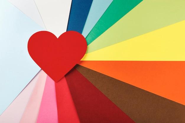 Coração vermelho em um fundo de muitos cartolinas coloridas