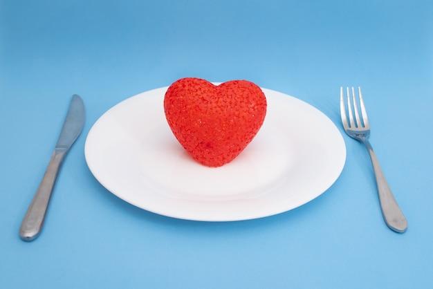 Coração vermelho em um prato branco e talheres em um fundo azul