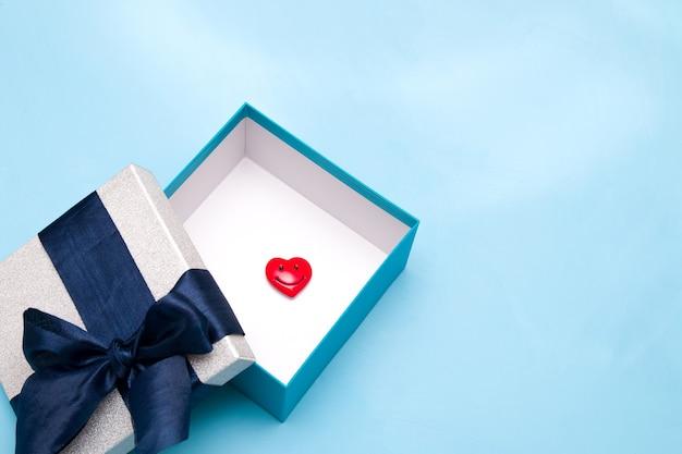 Coração vermelho em uma caixa de presente, fundo azul, espaço de cópia