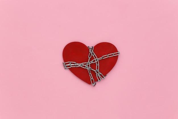 Coração vermelho enrolado em uma corrente de aço no fundo rosa