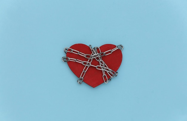 Coração vermelho envolto em uma corrente de aço em um fundo azul