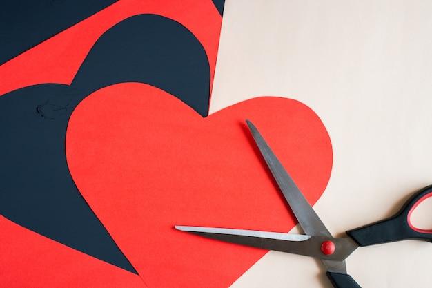 Coração vermelho esculpida em tesoura e folha de papel