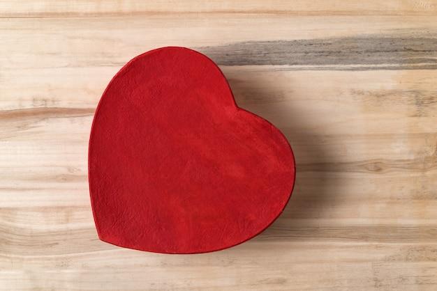 Coração vermelho estilo vintage em forma de caixa na mesa de madeira marrom. diretamente acima. presente para o dia dos namorados