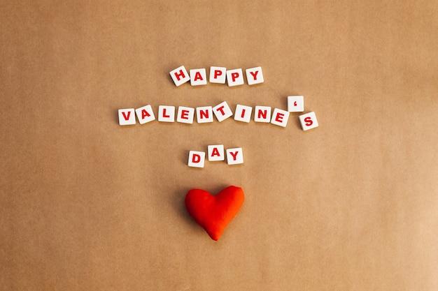 Coração vermelho feito à mão ao lado do texto de feliz dia dos namorados em fundo de papel kraft.
