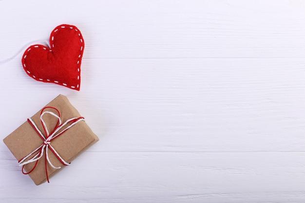 Coração vermelho feito de feltro e artesanal, em uma mesa de madeira branca