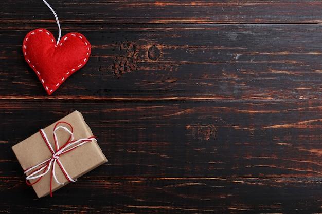 Coração vermelho feito de feltro e presente artesanal em uma mesa de madeira branca, conceito, banner, espaço de cópia.