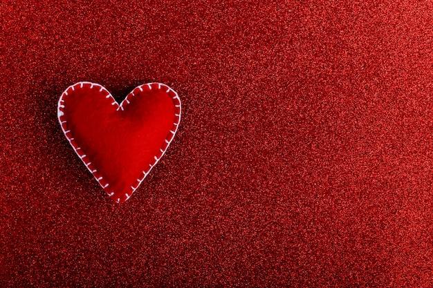 Coração vermelho feito de feltro sobre um fundo vermelho