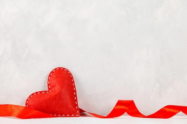 Coração vermelho, fita contra o de uma parede branca, conceito, um cartão postal para o dia dos namorados.