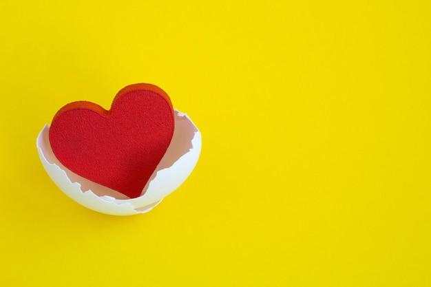 Coração vermelho na casca do ovo branco no amarelo